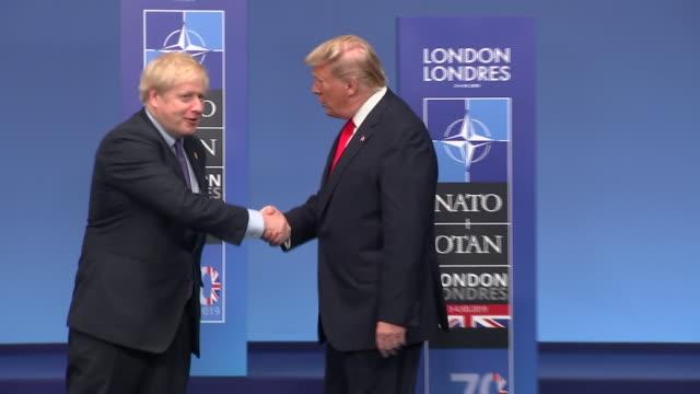interior views of prime minister boris johnson and nato general secretary jens stoltenberg greeting us president trump on the podium at the grove... - nato stock-videos und b-roll-filmmaterial