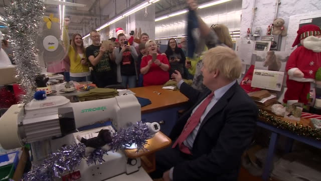 vídeos de stock e filmes b-roll de interior views of prime minister boris johnson doing some sewing on a machine at the john smedley factory and holding up a completed 'get brexit... - acabar