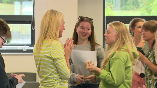 stockvideo's en b-roll-footage met interior views of school pupils collecting their a level exam results and talking congratulating each other about their grades at silverdale school... - testuitslag