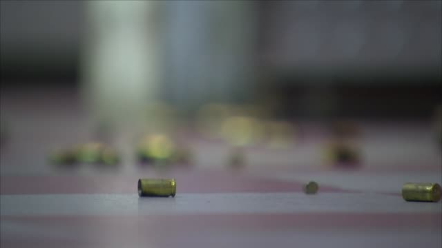 stockvideo's en b-roll-footage met interior views of spent gun cartridges on the floor of a shooting range - vuurwapenwinkel