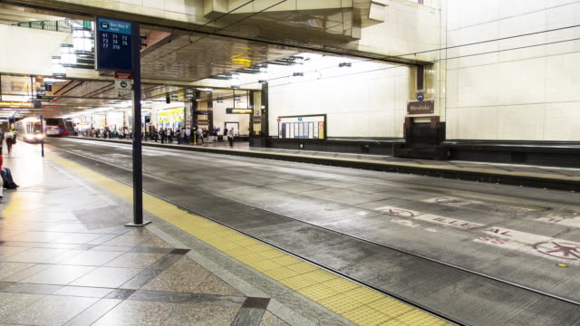 Interior W/S time lapse of commuters boarding public transit busses and trains in an underground tunnel station (Westlake Center Station) in Seattle, WA