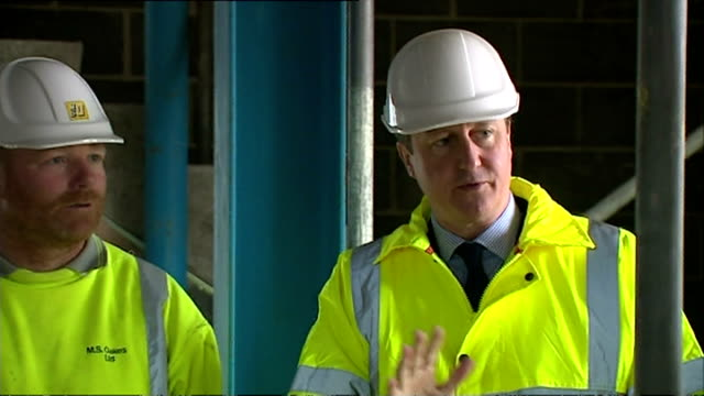 interiors and exteriors of british prime minister david cameron talking to construction workers while wearing hard hat and bright yellow hi vis... - ローストフト点の映像素材/bロール