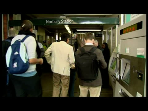 interiors British Transport Police Officers man metal detector machine inside Norbury station passengers passing through being scanned searched