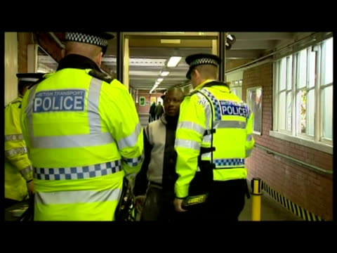 interiors british transport police officers man metal detector machine inside norbury station & passengers passing through being scanned & searched. - セキュリティスキャナ点の映像素材/bロール