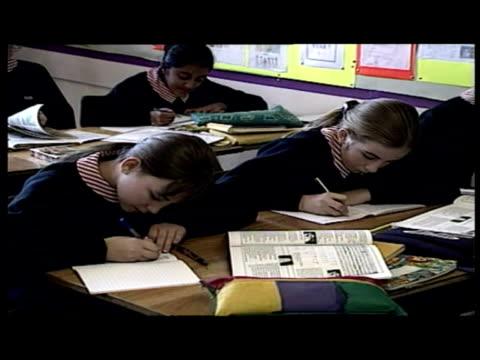 vídeos y material grabado en eventos de stock de interiors charlotte church in school uniform sits at desk in classroom working, writing in exercise book. - charlotte church
