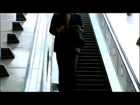 interiors commuters passing through ticket barriers & using escalators at canary wharf underground station. interiors police officers stand beside... - london docklands stock videos & royalty-free footage