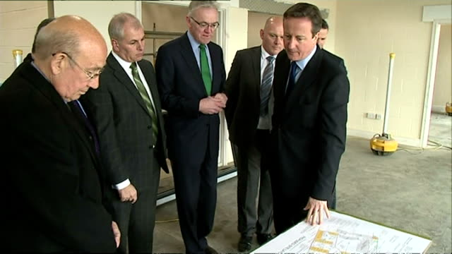 interiors of british prime minister david cameron arriving in room and talking to construction project managers and looking at plans with them on... - イーストアングリア点の映像素材/bロール
