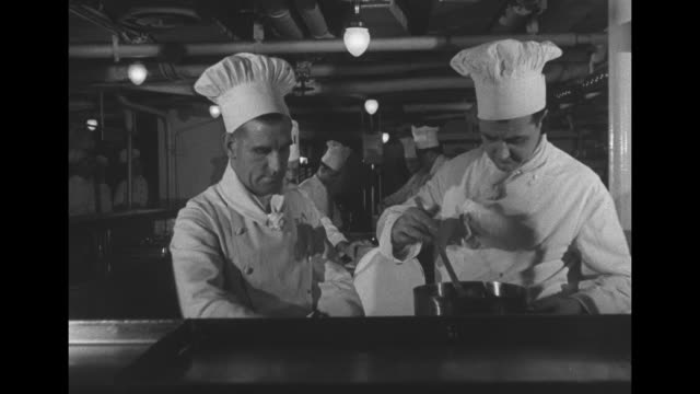 Interiors of RMS Queen Elizabeth / empty dining rooms / full dining room eating / kitchen with chefs preparing food / 2 chefs prepare 1 dish / CU...