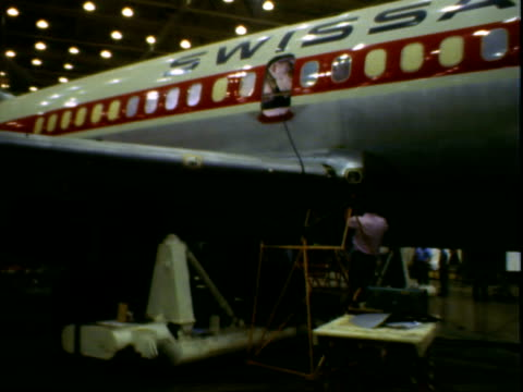 vídeos y material grabado en eventos de stock de interiors of unfinished plane with exposed insulation and wires men working / plane production activity inside hanger / man working on wing of plane... - cianotipo plano