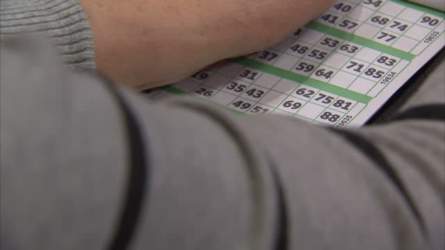 vídeos y material grabado en eventos de stock de interiors shows older elderly people playing in bingo hall with caller some digital games also being played hall has a bingo caller numbers being... - bingo