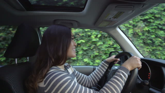 ms interiror shot of young woman driving a car - sitting stock videos & royalty-free footage