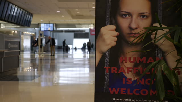 internal shots hartsfieldjackson atlanta international airport people walking in background with antisex trafficking sign saying human trafficking is... - trafficking stock videos and b-roll footage