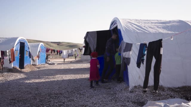 internally displaced family from mosul walks in their tent located inside a refugee camp in northern iraq thousands of civilians have fled the city... - isis stock videos and b-roll footage