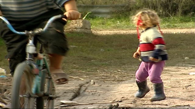 International adoption ban may be lifted Young Romanian girl running in dirt track road Gril running up towards Constantine and group of children...