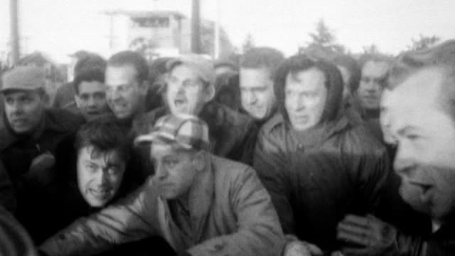 international association of machinists strike at republic aviation plant factory / large crowd of upset men huddle around a car / car tries to drive... - fackförbund bildbanksvideor och videomaterial från bakom kulisserna