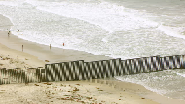 WS ZO AERIAL POV International border fence and California beach foreground extending into surf with beachgoers and Tijuana Mexico shoreline in background / San Diego, California, United States