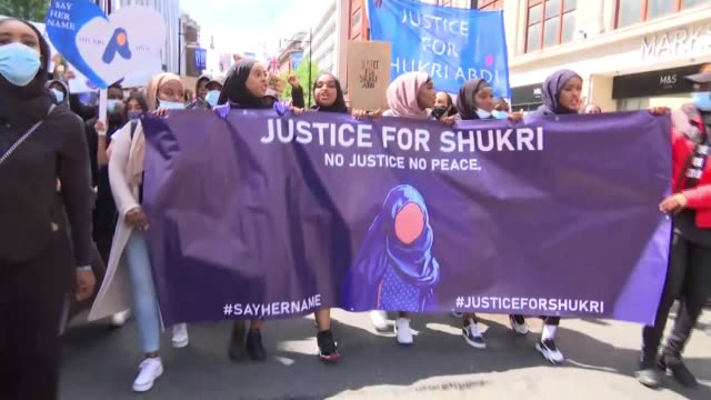 international demonstrations call for justice for 12 year-old shukri abdi; england: london: ext backwards tracking shot demonstrators along towards... - over the shoulder stock videos & royalty-free footage
