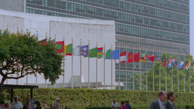 international flags blowing in wind in front of un building / nyc - united nations building stock videos and b-roll footage