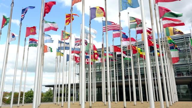 international flags vor einem business-gebäude - messen stock-videos und b-roll-filmmaterial