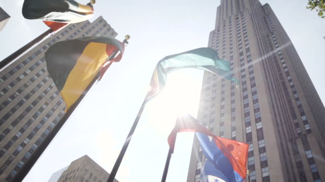 international flags outside of new york city's rockefeller center - establishing shot - summer 2016 - rockefeller center video stock e b–roll