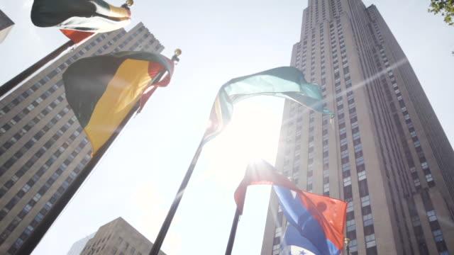 vídeos de stock, filmes e b-roll de international flags outside of new york city's rockefeller center - establishing shot - summer 2016 - centro rockefeller