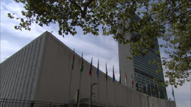 vídeos de stock, filmes e b-roll de international flags stand in front of the united nations building in new york city. - united nations