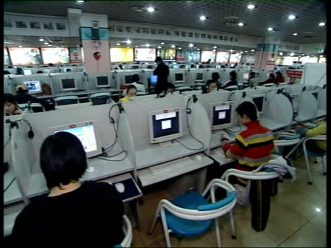 internet blogs defy authority of chinese government; lights flashing on computer server pull focus young people using computers in internet cafe... - internet café stock-videos und b-roll-filmmaterial
