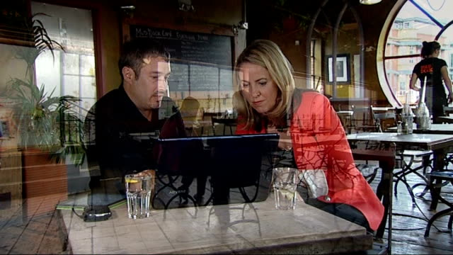fake facebook 'likes' scam cost to businesses and charities mark mcandrew and reporter sittgin in cafe looking at laptop computer - fake stock videos & royalty-free footage