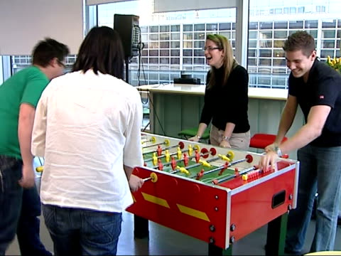 google offices england london int staff working for internet giant google playing table football in staff restaurant / staff sat using laptop... - bean bag stock videos & royalty-free footage