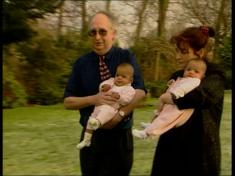 internet twins; itn england: chester ext allen kilshaw and judith kilshaw along thru hotel grounds holding baby twins kimberly and belinda - 英国チェスター点の映像素材/bロール