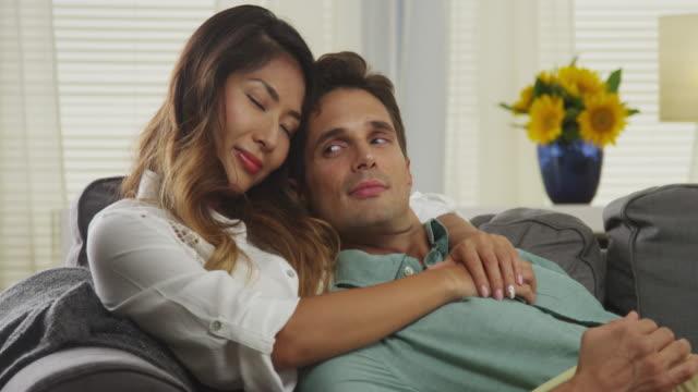 vídeos y material grabado en eventos de stock de interracial couple cuddling on couch - bronceado