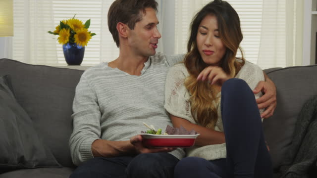 Interracial couple eating chips and dip