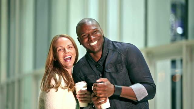 vídeos de stock, filmes e b-roll de casal interracial segurar copos de café, caminhar para a câmera - de braços dados