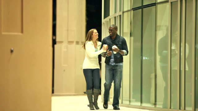 vídeos de stock, filmes e b-roll de casal interracial em uma noite, andando através da construção de - de braços dados