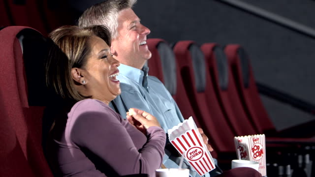 Interracial couple watching movie in theater