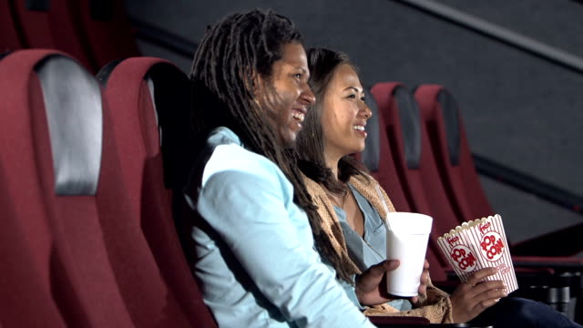 interracial couple watching movie in theater - african american culture stock videos & royalty-free footage