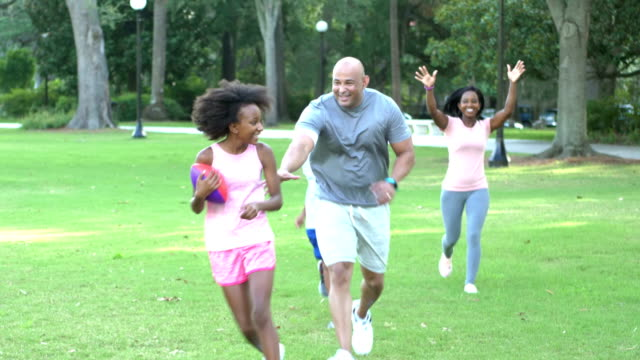 interracial family in park, girl running with football - american football ball stock videos & royalty-free footage