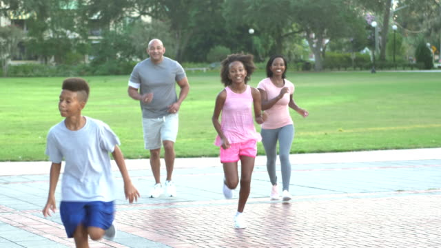 interrassische familie läuft im park zusammen - 4 5 years stock-videos und b-roll-filmmaterial