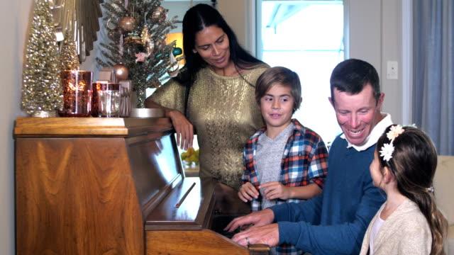 interracial family singing, dad playing piano, christmas - carol singer stock videos & royalty-free footage