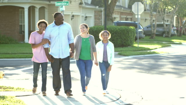interracial family taking walk together, crossing street - family with two children stock videos & royalty-free footage