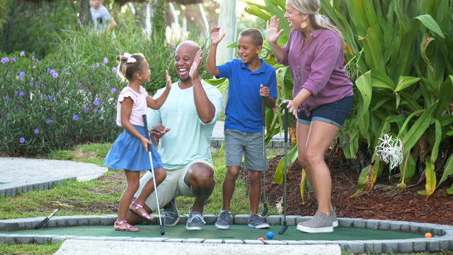 interracial family, two children playing miniature golf - putting stock videos & royalty-free footage