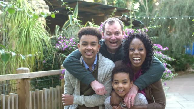 stockvideo's en b-roll-footage met interracial familie met twee jongens in park - 35 39 years