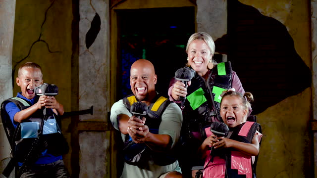 interracial family with two children playing laser tag - 4 5 years stock videos & royalty-free footage