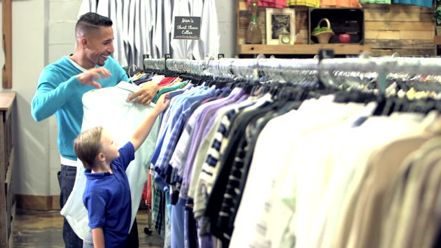 Interracial father and son shopping in clothing store