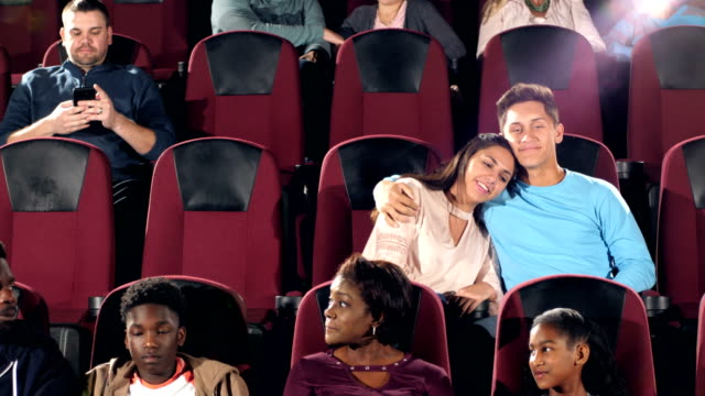 interracial teenage couple in movie theater, arm around - teenage couple stock videos & royalty-free footage