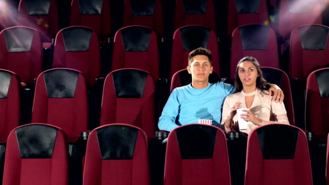 interracial teenage couple watching movie in theater - pacific islander stock videos & royalty-free footage