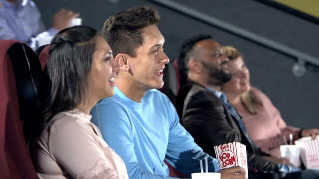 Interracial teenage couple watching movie, laughing