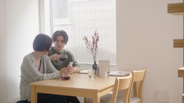 スマートフォンを使用しながら朝のコーヒーを飲む異人種間の若いカップル - 日課点の映像素材/bロール