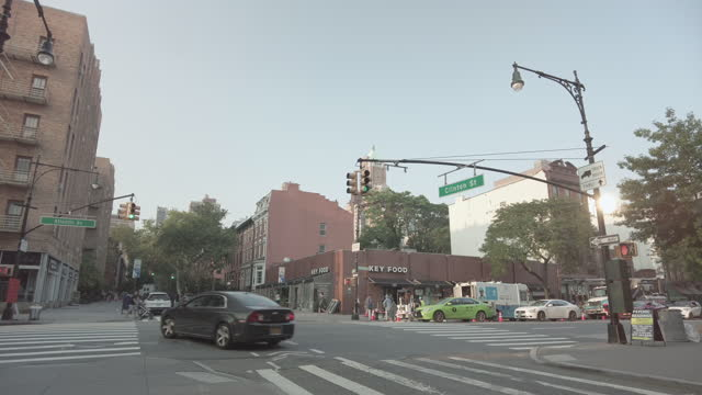 intersection of atlantic avenue and clinton street in brooklyn with traffic, a taxi, a person with a stroller, a food delivery person and pedestrians... - yellow taxi stock videos & royalty-free footage