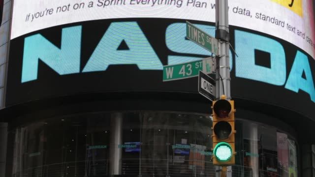 intersection of times square and 43rd street sign / traffic light with nasdaq entrance in the background times square intersection on february 27,... - ナスダック点の映像素材/bロール